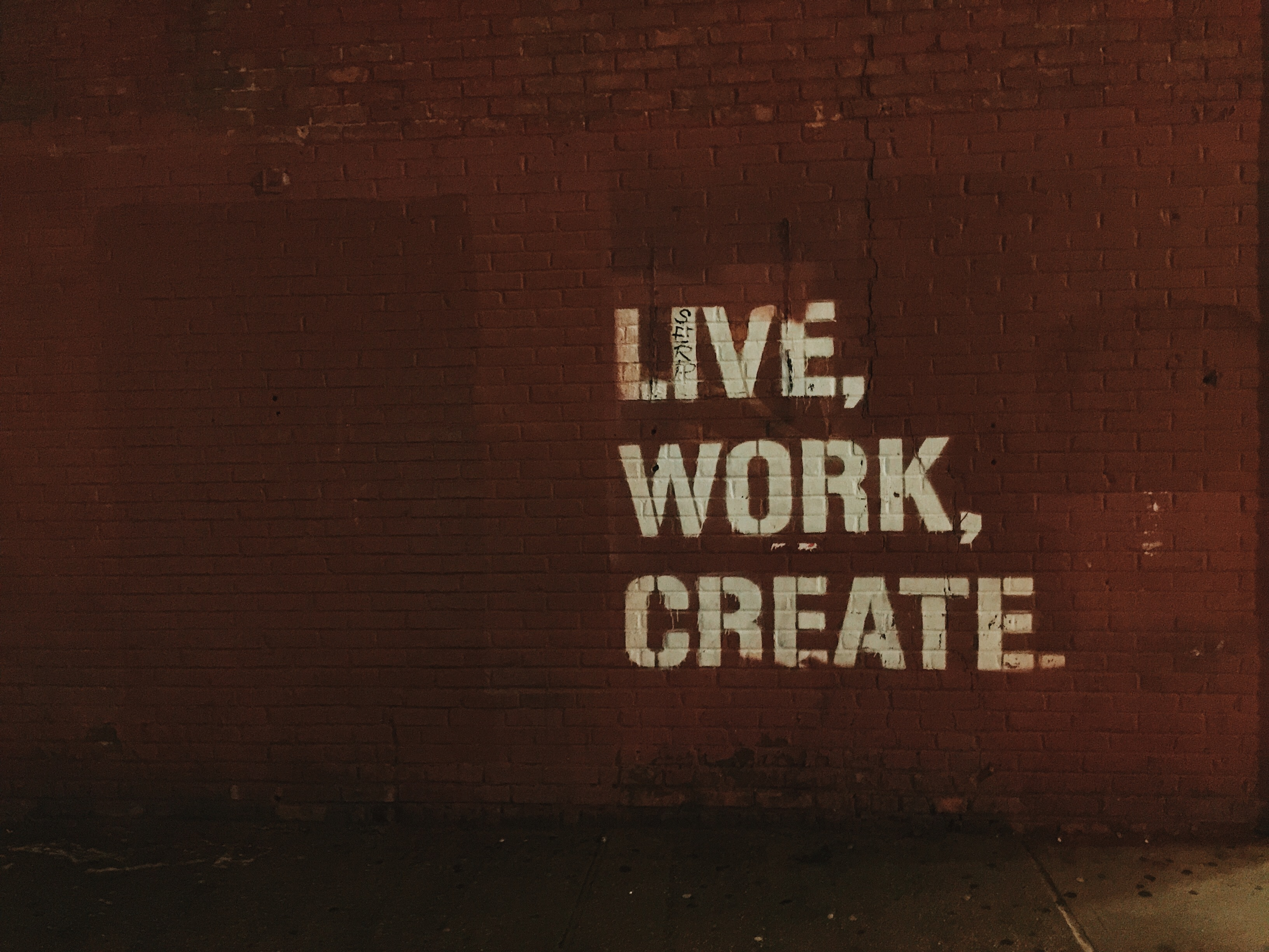 "A brown brick wall with the words ""Live. Work. Create."" spraypainted on it."